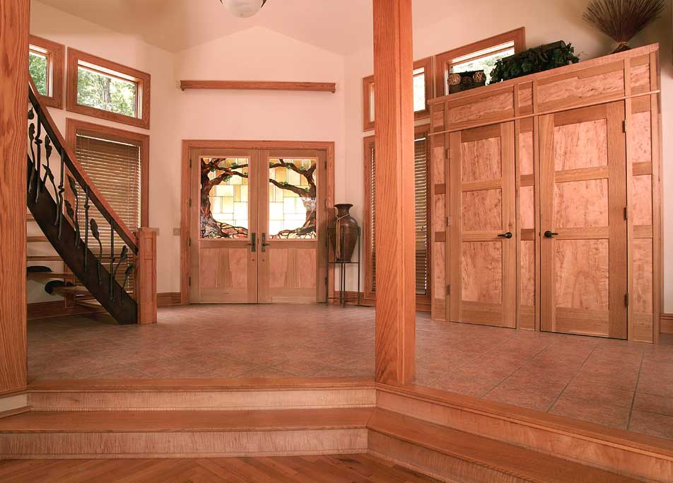 This foyer features a custom double front door in white curly maple. The built in coat cabinet of ambrosia maple and quartersawn white oak. The stainglass and forged balustrade were commissioned (see Blair House at corlisdesign.com)