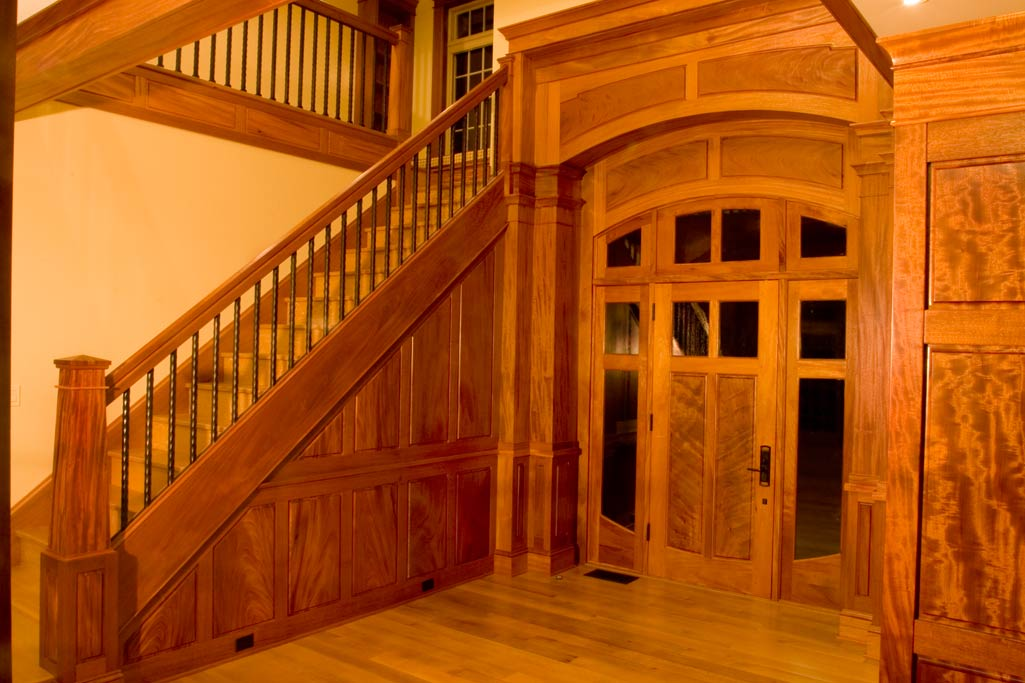 Entry foyer to Artisan House. The arched panels above the door were paneled with the grain arching in the same radius. A theme of pairs is present through this room.