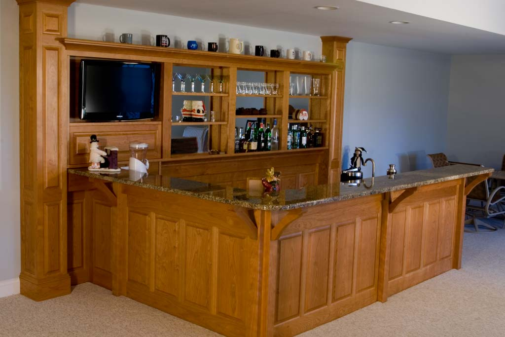 A solid cherry bar with a back bar of columns and paneling.