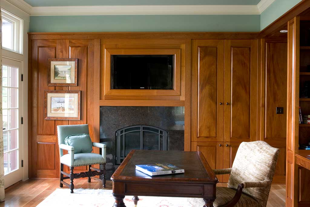 A mahogany study using bookmatched panels and housing an entertainment center and media storage.