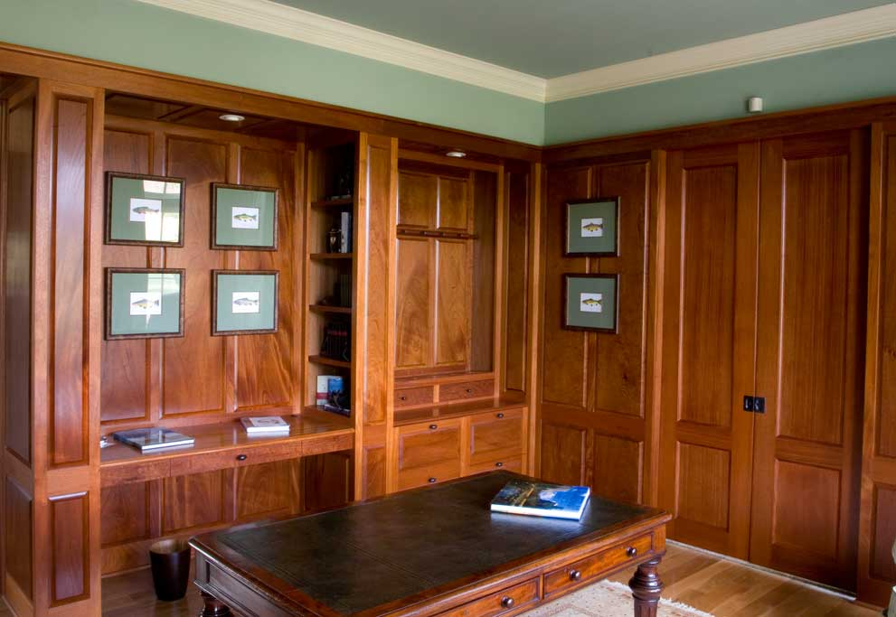 This mahogany study shows a built in back desk with a computer printer hidden in a pullout drawer located below a gun display rack. Pocket doors lead to the master bedroom suite beyond.