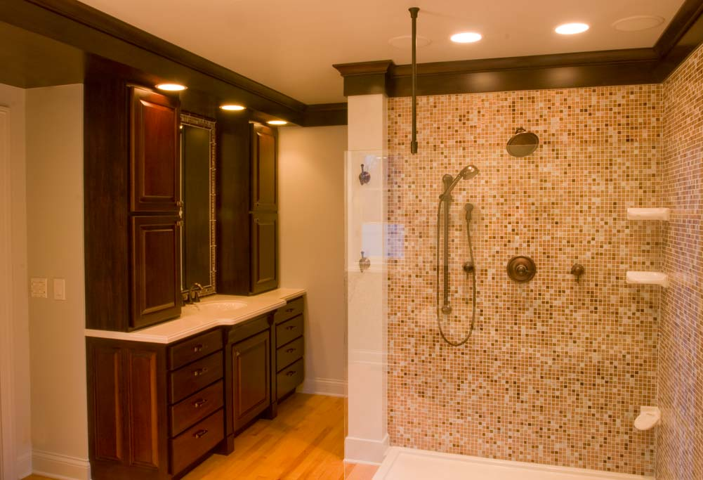 Maple floor, mahogany cabinets, paneling and two piece crown molding with a background of glass mosaic tile.