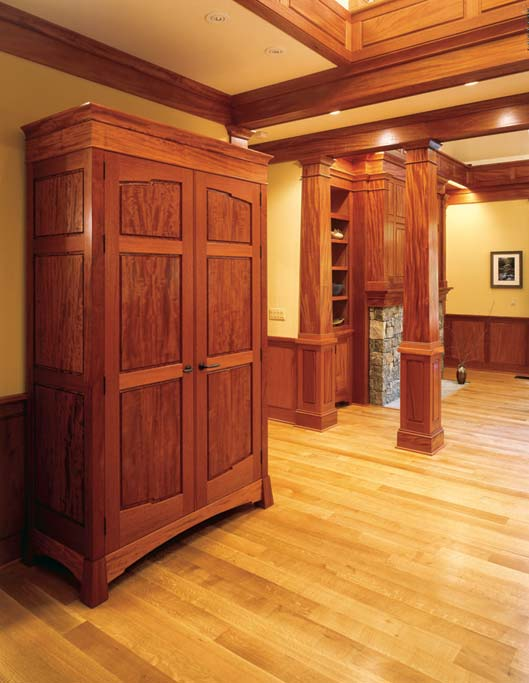 The armoire serves as an entry coat closet. It features very rare beeswing figure mahogany framed by straight grained materials to not compete with the panels.