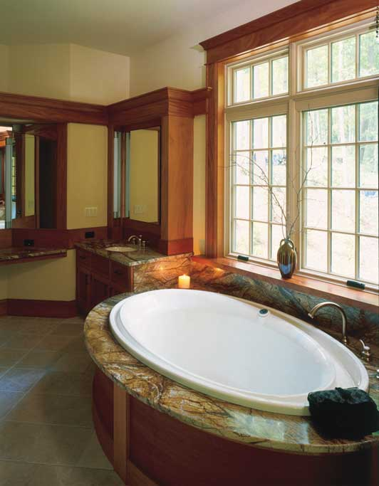 "In this master bathroom in the woods we used ""rainforest marble"" with mahogany built ins and vanities."