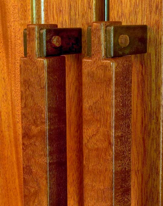 These refrigerator handles show our willingness to mix materials when appropriate. To make the conection to the wood paneled front of the fridge, we utilized solid brass which was hammered and a craftsman era patina applied. The mahogany handles were pegged in an open bridle joint.