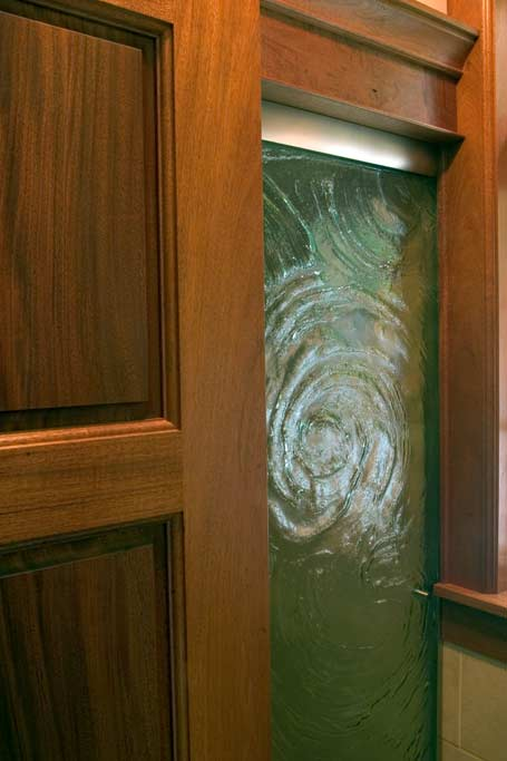 This cast art glass was utilized to create a light wall. It is framed with mahogany.
