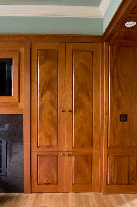 These mahogany doors open and slide back into the wall to expose the entertainment equipment and media.