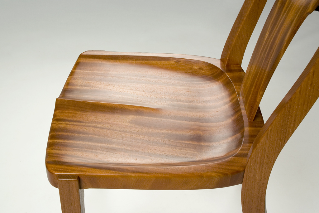 A close up of the hand scraped and carved seat showing the wonderful ribbon grain mahogany.