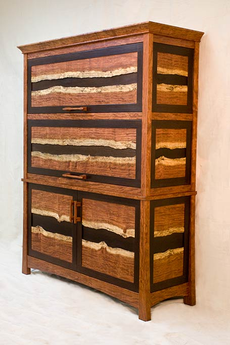 A regular client of ours wanted a special gun cabinet for his son.  They visited the shop and we showed them something we were playing with, using the natural edge of the Bubinga tree, we designed a large gun cabinet to feature the spalted edge of this incredible wood. Normally this is cut off and not used, but it was beautiful and inspired this case.  The dark wood is quarter sawn Wenge.   The two upper doors are barrister style, retracting back into the case to expose pull out gun display racks.
